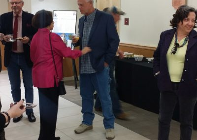 photo of george mendoza talking with someone at his art show