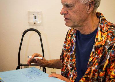 george mendoza signing a copy of his book