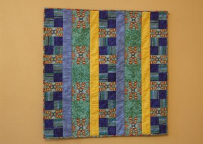 picture of mendoza's work with squares and vertical blue and yellow lines throughout