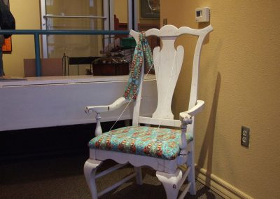 white chair with mendoza's work on the fabric of the seat of the chair