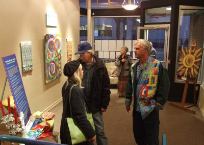 photo of mendoza talking with someone at his art show