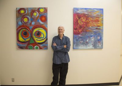 mendoza posing and smiling in front of his paintings