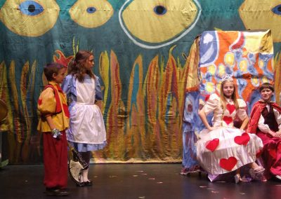 alice at her trial before the queen and king of hearts