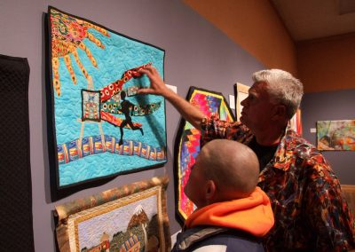photo of mendoza touching one of his quilting works
