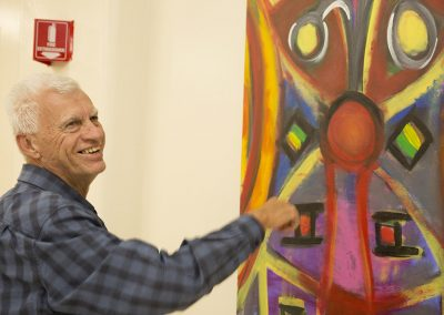 mendoza smiling in front of his painting