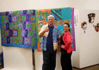 mendoza posing with a woman in front of his artworks