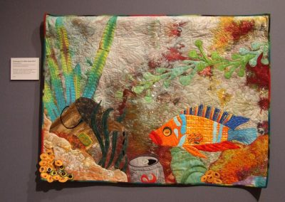 photo of mendoza's quilting work with a fish in a polluted ocean
