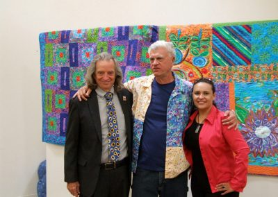 mendoza posed with a man and a woman in front of his artworks