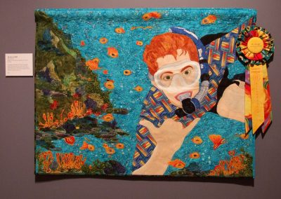 photo of mendoza's quilting work with a man scuba diving