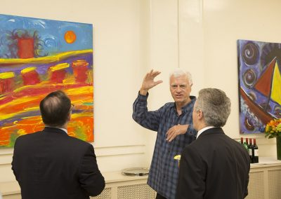 mendoza explaining his artwork with two people observing his art
