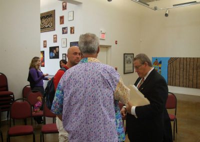 photo of mendoza speaking with two people at the gallery