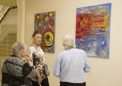 people observing and discussing mendoza's artwork