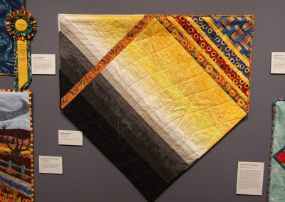 photo of mendoza's quilting work with black, yellow, and grey and abstract lines