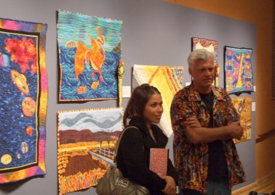 photo of mendoza posing with someone in front of his quilting works