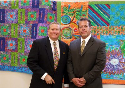 two men posed in front of mendoza's artwork