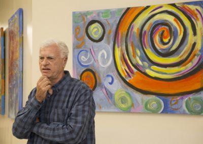 mendoza speaking in front of his artwork