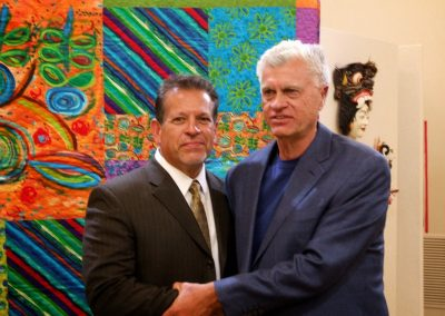 mendoza posed with a man in front of his artwork