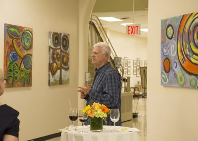 mendoza speaking in front of his artworks