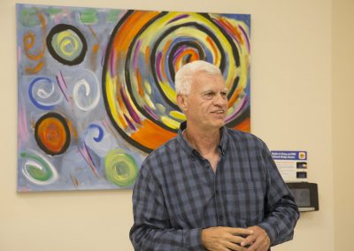 mendoza smiling and speaking in front of his artwork
