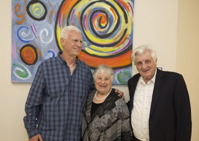 mendoza posed with a woman and a man in front of his painting