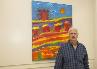 mendoza posed in front of his artwork