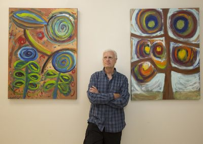 mendoza with his arms crossed posed in front of his paintings